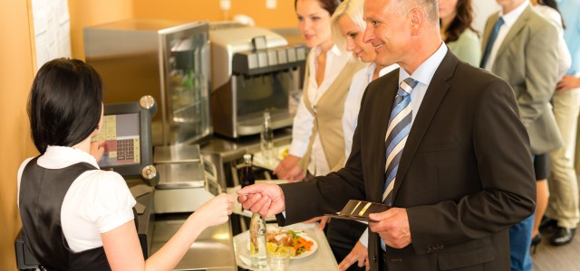 Cafeteria man pay by credit card cashier food on serving tray