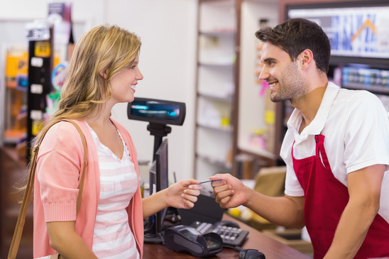 photodune-12085616-smiling-woman-at-cash-register-paying-with-credit-card-in-supermarket-xs